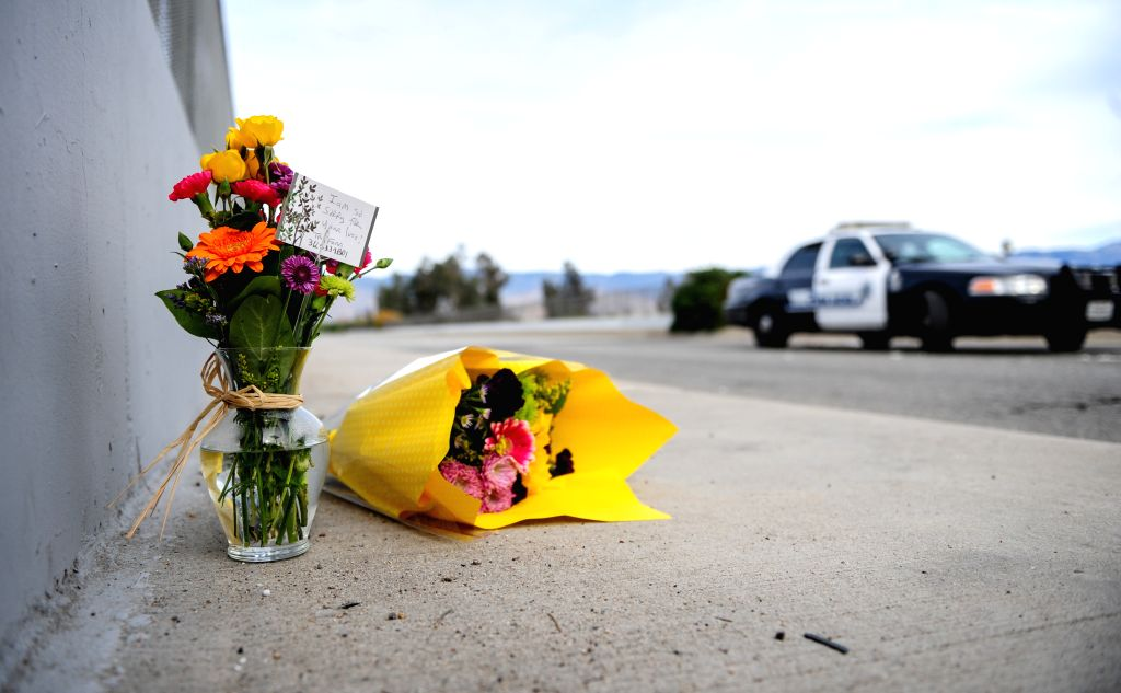 Flowers are left by the side of the road as police blocks the road leading to the site of the mass shooting in San Bernardino, California, Dec. 3, 2015. ...