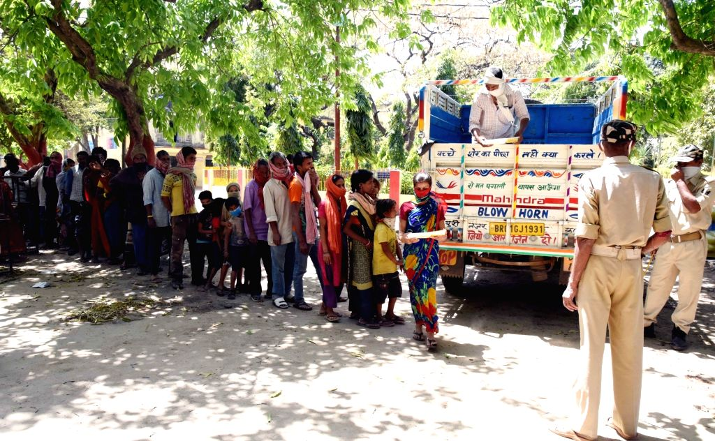 Food being distributed among migrant workers at a relief camp set up for them at the College of Commerce, Arts & Science during a 21-day nationwide lockdown imposed to contain the spread ...