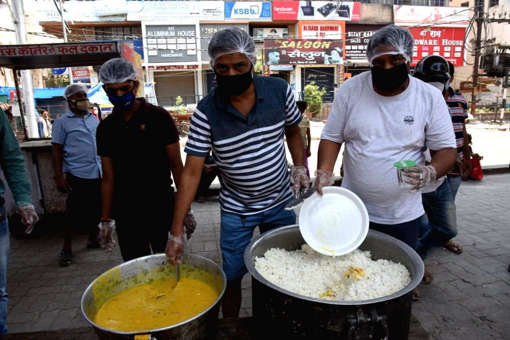 Food being distributed among poor, needy and homeless people maintaining social distancing in Patna during the extended nationwide lockdown imposed to mitigate the spread of coronavirus; on ...