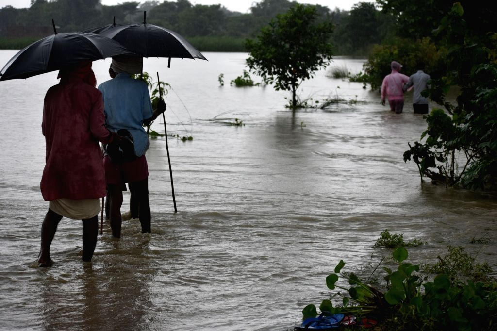 Forbesganj: People wade through flood waters to higher places in Forbesganj, Araria district of Bihar on July 13, 2019. (Photo: IANS)