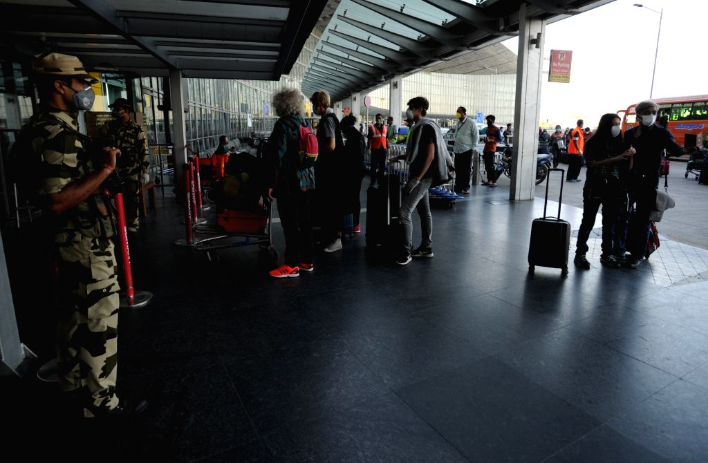 Foreign nationals wearing facemasks line up outside the departure terminal of the Netaji Subhash Chandra Bose International Airport to board a special evacuation flight on Day 7 of the ...