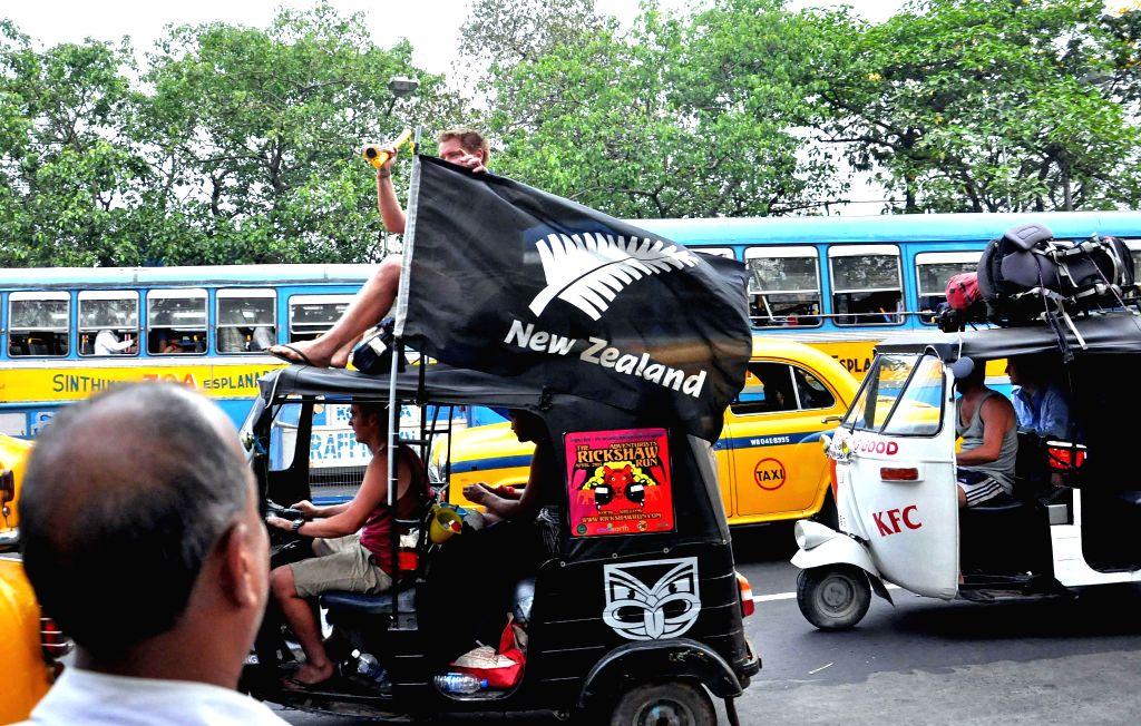 Foreign tourists enjoy a ride on an auto rickshaw in Kolkata on April 13, 2014.