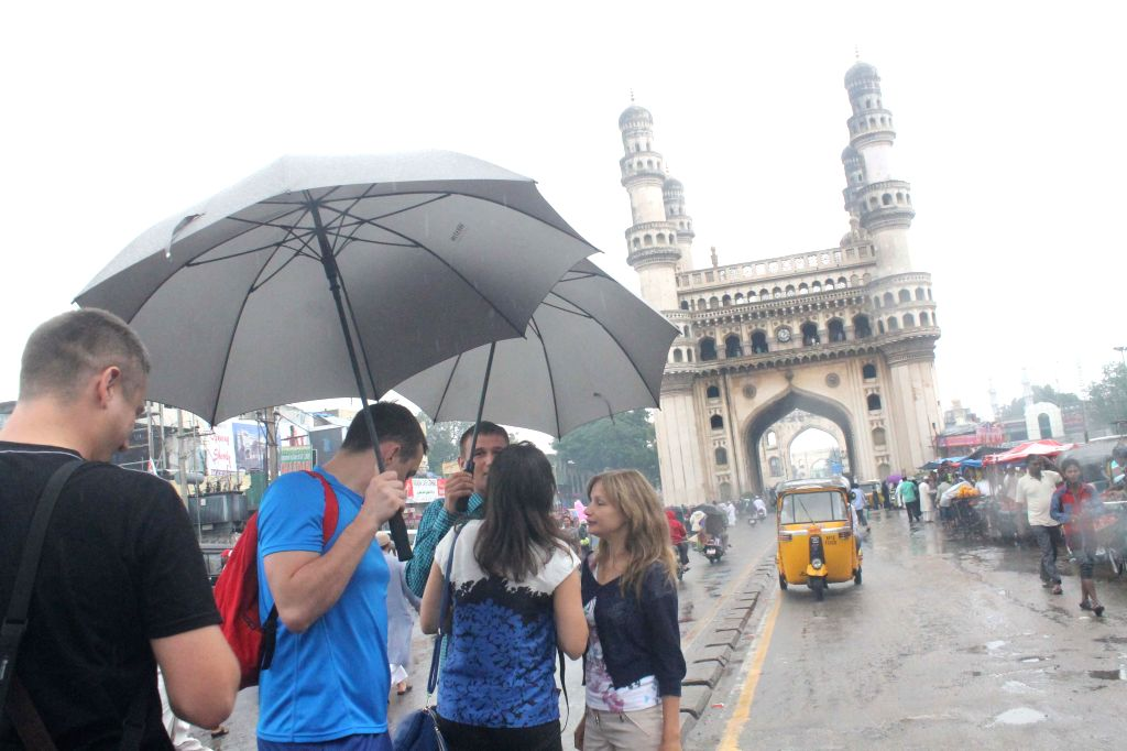 Foreign tourists enjoy themselves during rains at Charminar in Hyderabad on Aug 29, 2014. (Photo: IANS)