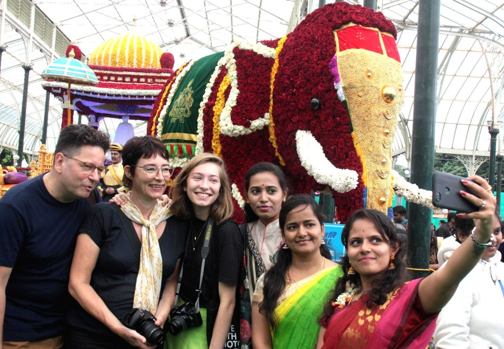 Foreign tourists pose for selfies at the inauguration of Annual Flower Show that will be a part of Independence Day celebrations, at the Lalbagh Botanical Garden in Bengaluru on Aug 9, ...