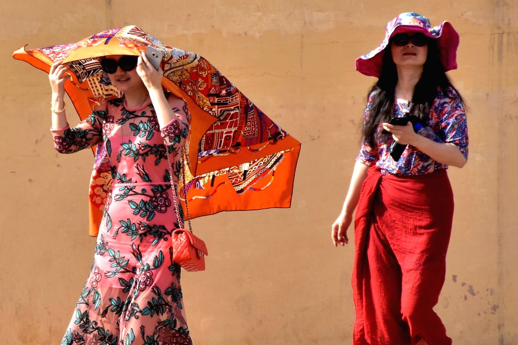 Foreign tourists shield themselves from direct sun on a hot day in Jaipur on May 16, 2017.