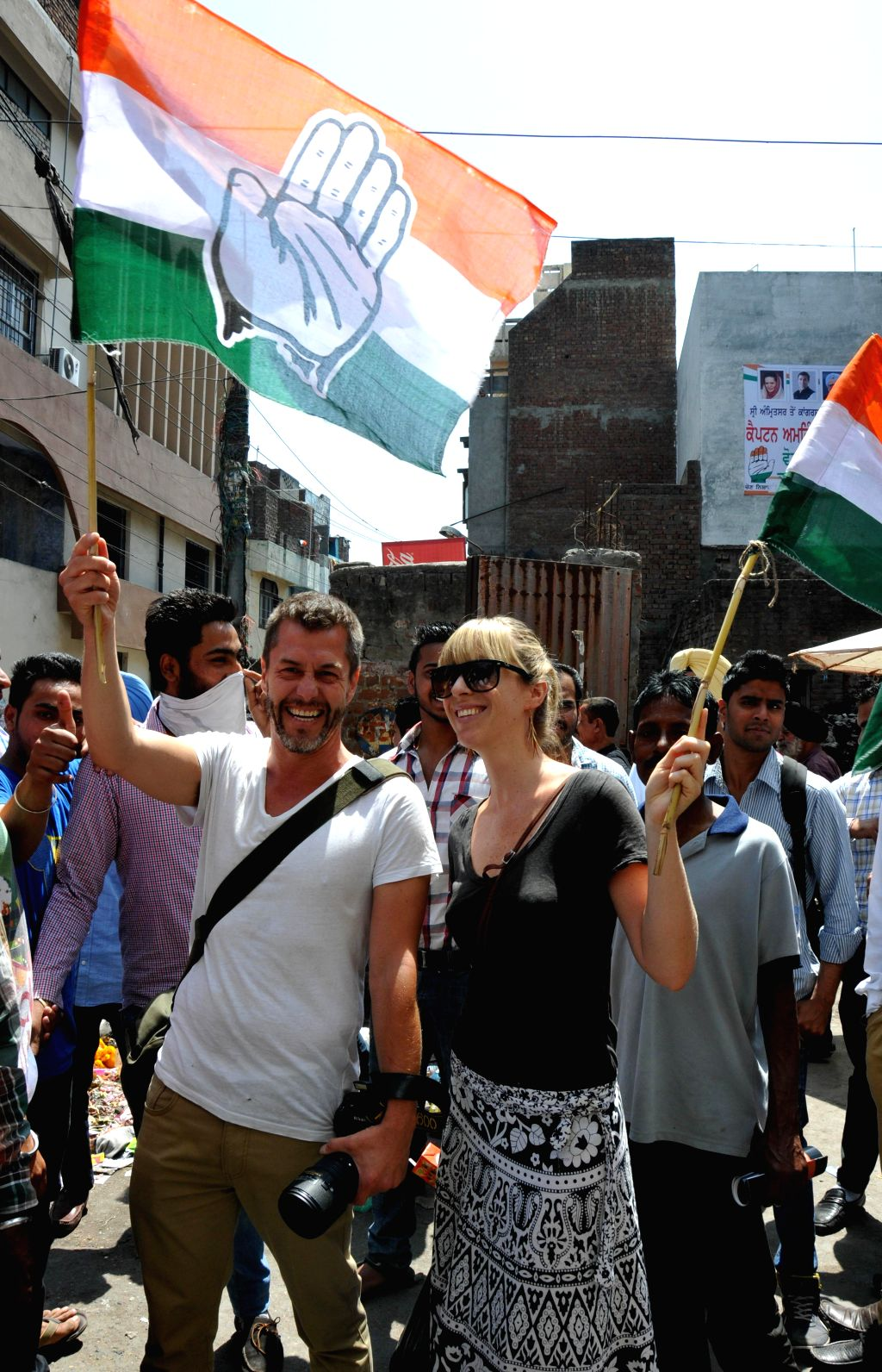 Foreigners holding Congress flags participate in a roadshow of Congress candidate for 2014 Lok Sabha Election from Amritsar, Captain Amarinder Singh in Amritsar on April 16, 2014. - Amarinder Singh
