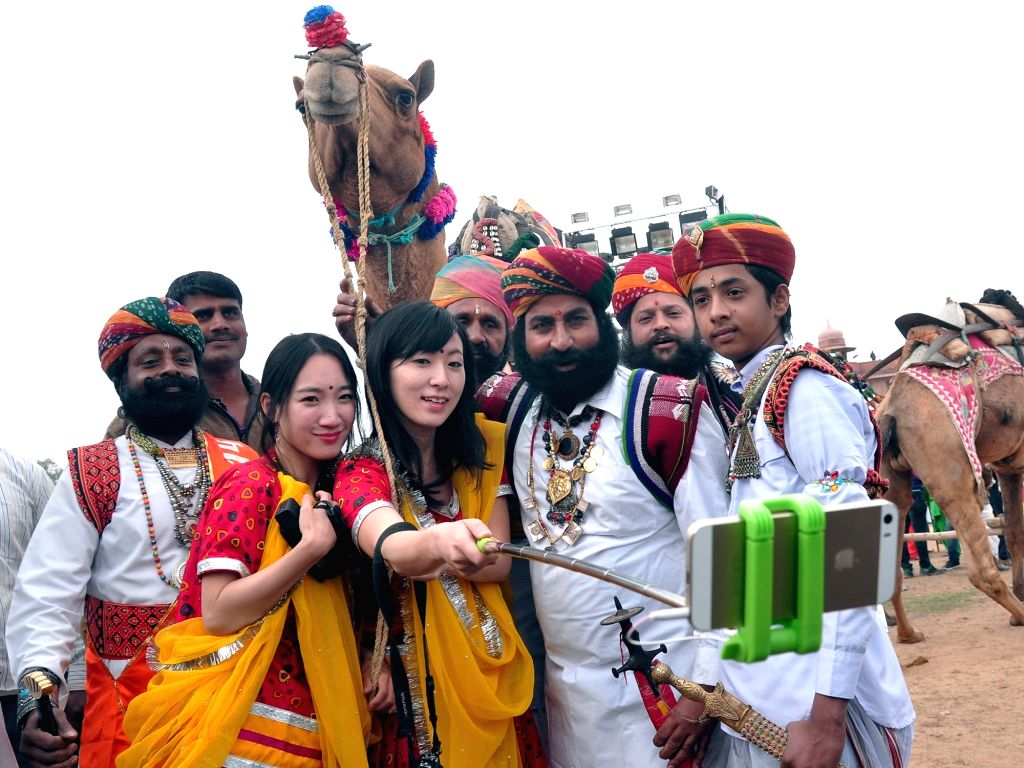 Foreigners take selfies with camel and men dressed in traditional Rajasthani attire during the International Camel Festival in Bikaner, on Jan 14, 2017.
