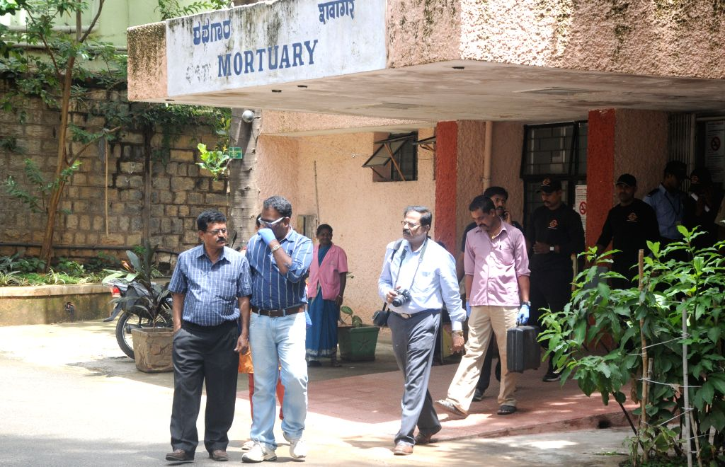 Forensic experts come out from the Mortuary at National Institute of Mental Health and Neurosciences (NIMHANS) where an under-treatment 22-year-old prisoner on 16th Aug, 2015 snatched a ...