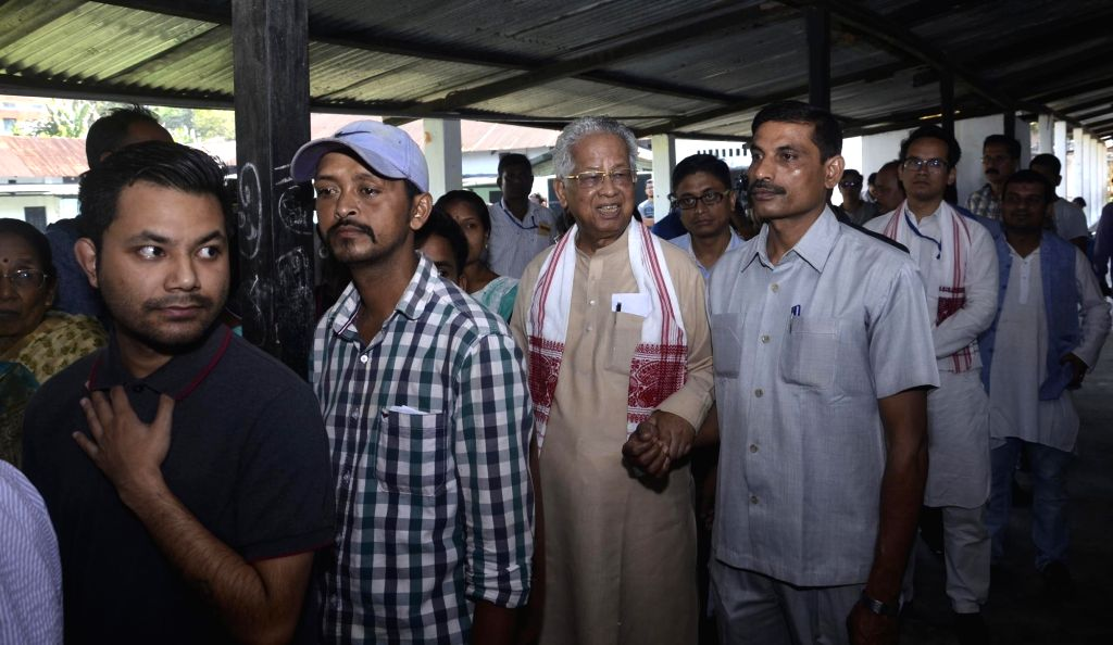 Former Assam Chief Minister Tarun Gogoi and son, Congress' Lok Sabha candidate from Kaliabor, Gaurav Gogoi stand in queue to cast vote for Lok Sabha election at a polling station, in Assam's ... - Tarun Gogoi