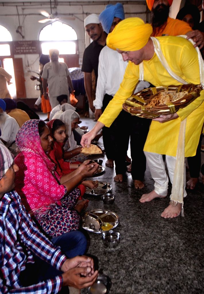 Former Australian cricketer Brett Lee helps in the distribution of  'langar' during his visit to the Golden Temple in Amritsar on May 29, 2018.