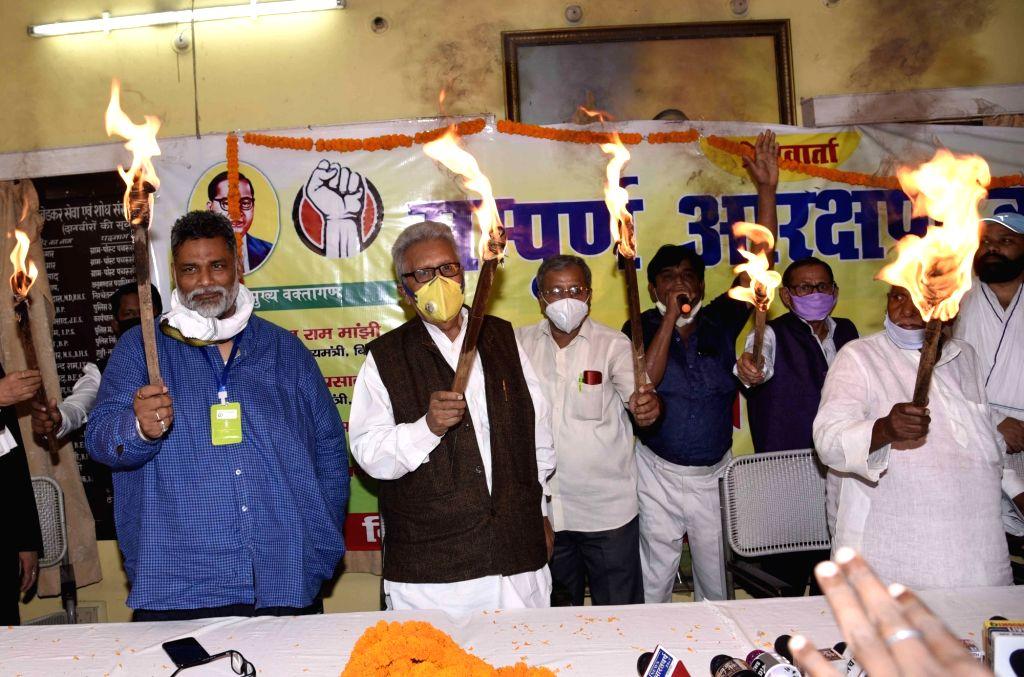Former Bihar Chief Minister Satish Prasad and Jan Adhikar Party president Rajesh Ranjan alias Pappu Yadav hold torch lights at the launch of  'Sampoorn Arakshan  Kranti' , in Patna on July 5, ... - Satish Prasad and Pappu Yadav