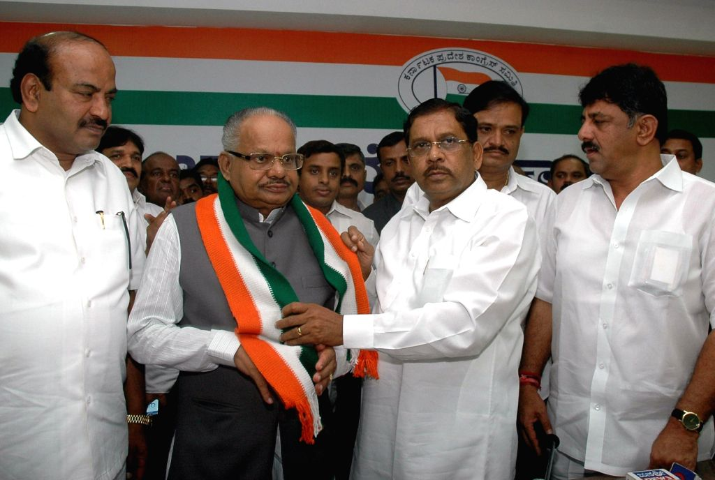 Former BJP MLA and MP M Srinivas who formally joined Congress is being welcomed by G Parameshwar President KPCC at Congress Office in Bengaluru on  August 14, 2013. (Photo:::IANS)