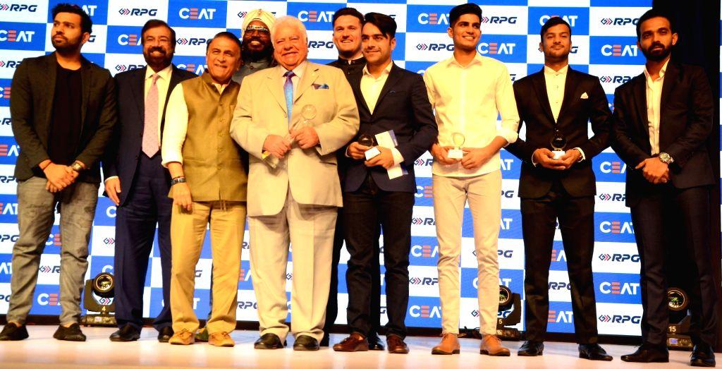 Former cricketers Sunil Gavaskar and Farokh Engineer with cricketers Rohit Sharma, Chris Gayle, Colin Munro, Rashid Khan, Shubman Gill, Mayank Agarwal and Ajinkya Rahane during Ceat cricket ... - Rohit Sharma and Rashid Khan