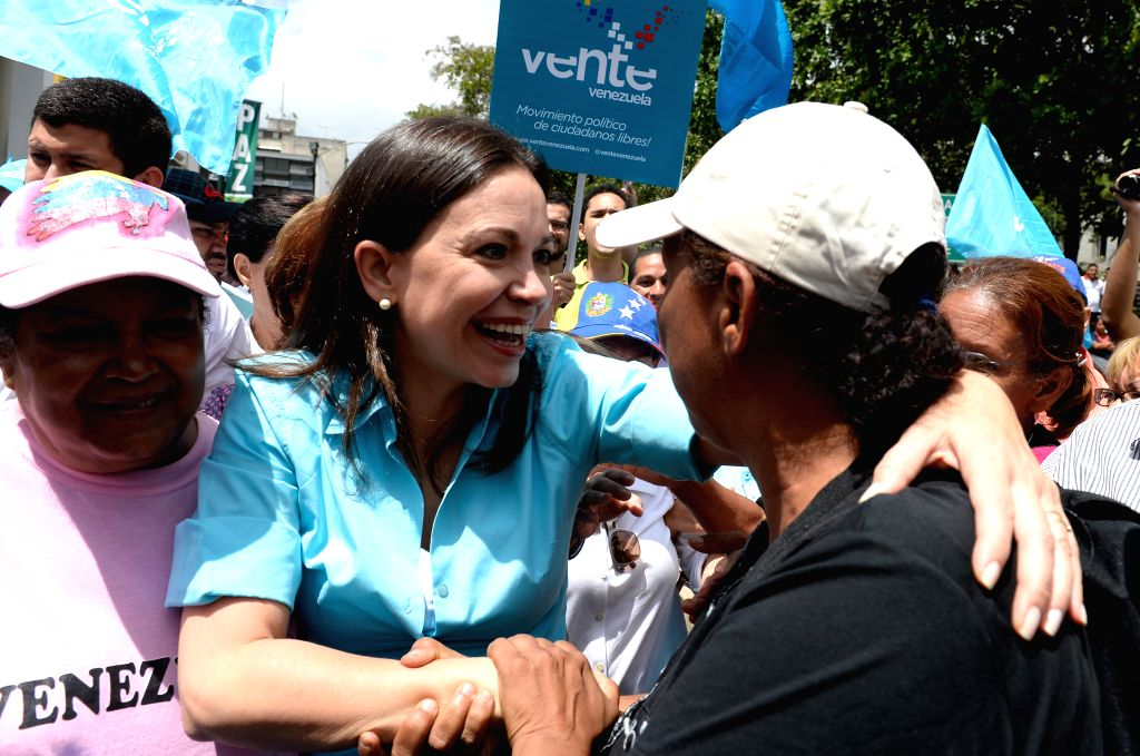 Former Deputy of Venezuela's National Assembly (NA) Maria Corina Machado (L) greets her supporters in the office of the Main Electoral Board, in the city of Los ...