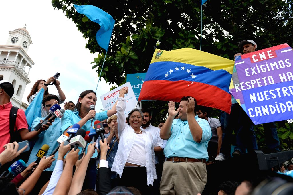 Former Deputy of Venezuela's National Assembly (NA) Maria Corina Machado rises the hand of Isabel Pereira (C), director of the Center for the Dissemination of ...