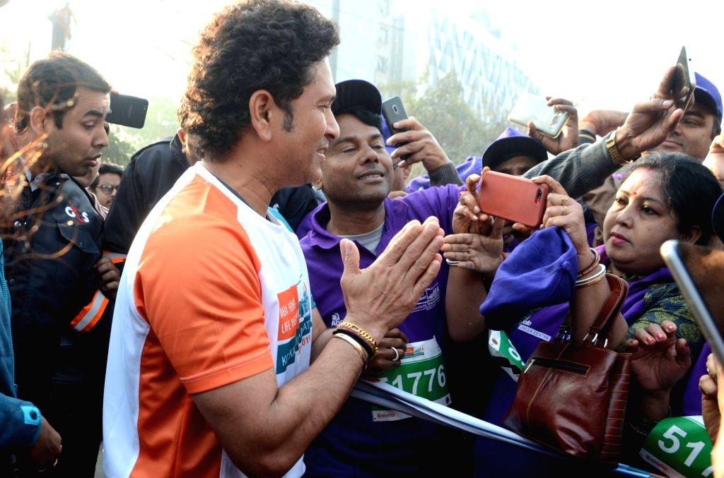 Former Indian cricketer Sachin Tendulkar greets the participants during the flagging off ceremony of IDBI Federal Life Insurance Kolkata Full Marathon, on Feb 3, 2019. - Sachin Tendulkar
