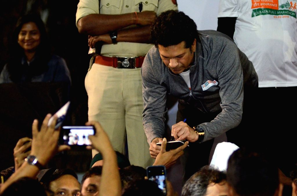Former Indian cricketer Sachin Tendulkar signs an autograph during the flagging off ceremony of IDBI Federal Life Insurance Kolkata Full Marathon, on Feb 3, 2019. - Sachin Tendulkar