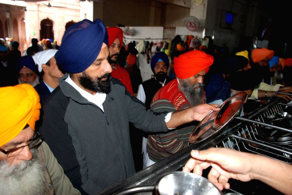 Former Minister and Akali leader Bikram Singh Majithia washes utensils as he performs 'seva' during his visit to the Golden Temple in Amritsar on Dec 12, 2019. - Bikram Singh Majithia