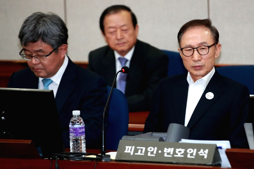 Former President Lee Myung-bak (R) sits in a courtroom at the Seoul Central District Court on May 23, 2018, as he attends the first hearing over bribery, embezzlement, tax evasion and other ...