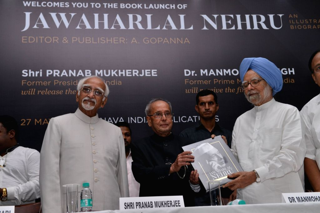 """Former Prime Minister Manmohan Singh receives a copy of A. Gopanna's book """"Jawaharlal Nehru: An Illustrated Biography"""" from former President Pranab Mukherjee during the launch of ... - Manmohan Singh and Pranab Mukherjee"""