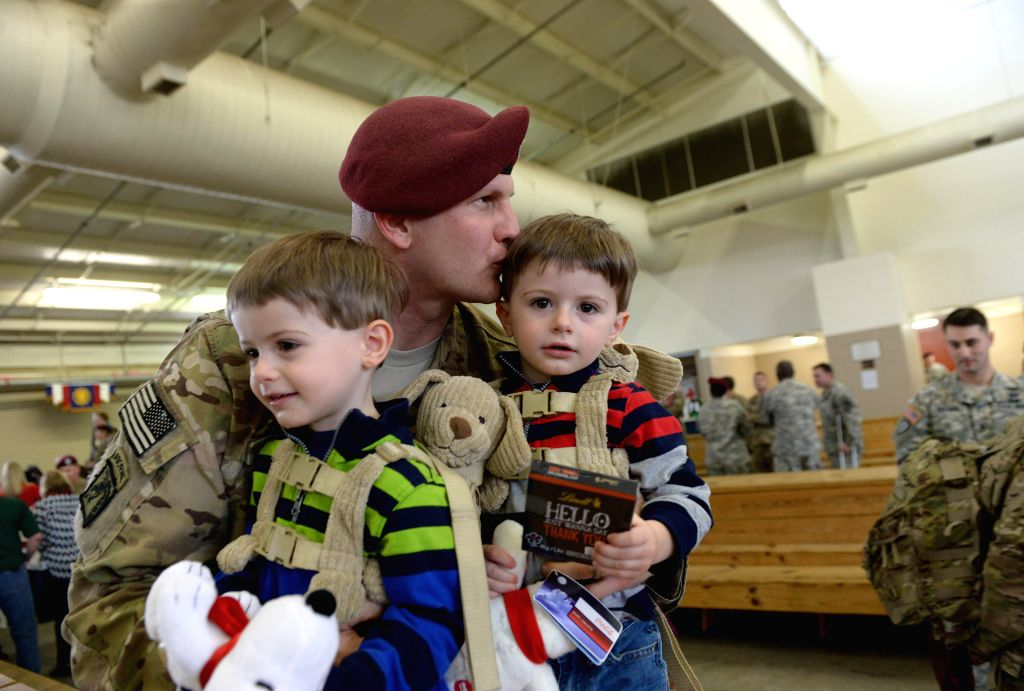 Fort Bragg (U.S.): Twins Jacob (L) and Alex welcome their father Marc Gaguzis, a soldier of the XVIII Airborne Corps returning from Afghanistan, at Fort Bragg, North Carolina, the United States, Dec.