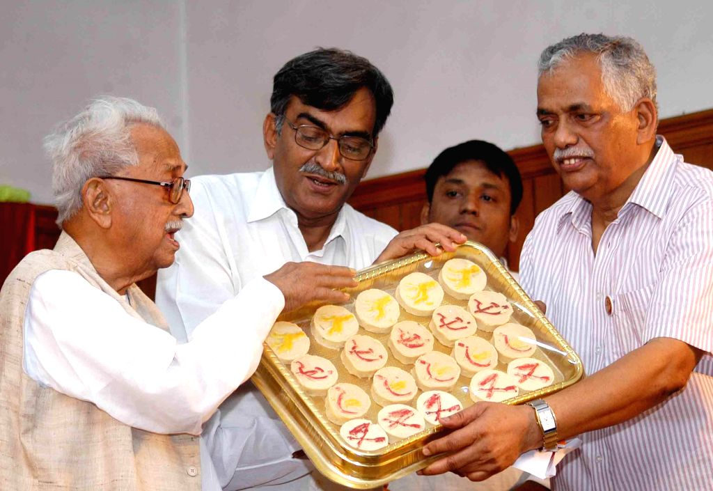 Forward Bloc leaders Ashok Ghosh and Debabrata Biswas with Communist Party of India-Marxist (CPI-M) leader Surya Kant Mishra celebrate 'Poila Baisakh' in Kolkata on April 15, 2014. - Ashok Ghosh and Kant Mishra