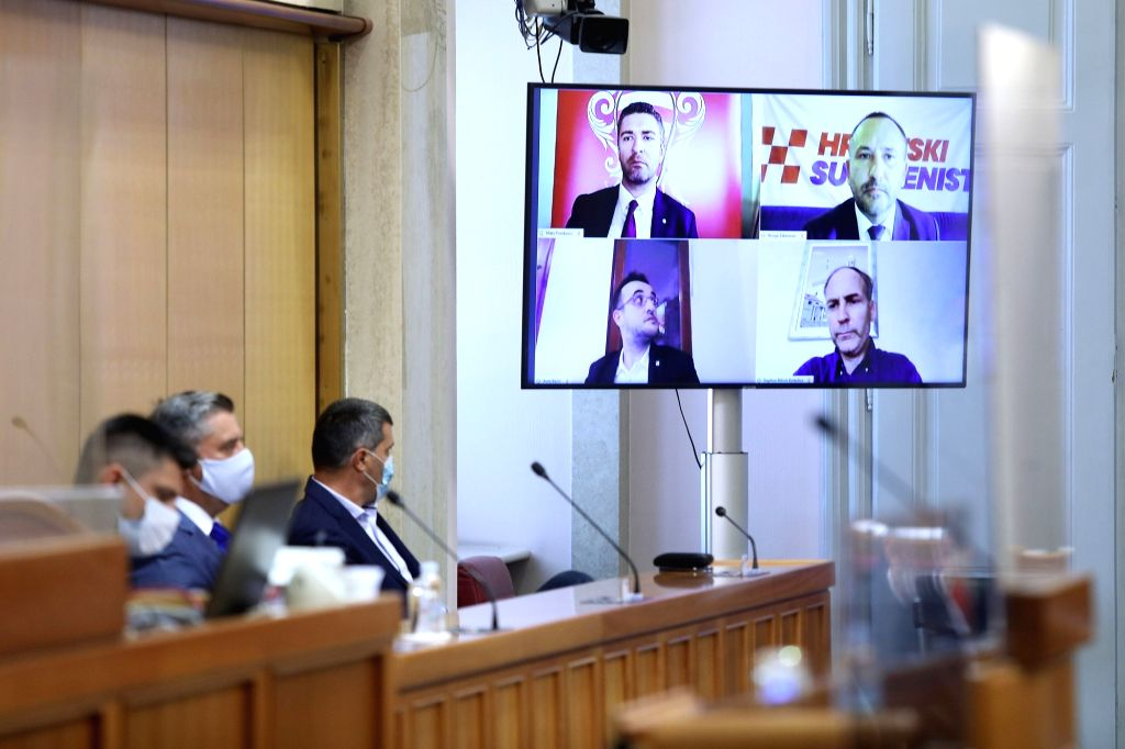 Four members of the Croatian parliament, who are in self-isolation after testing positive for COVID-19, take part in a parliament voting via video streaming in ...