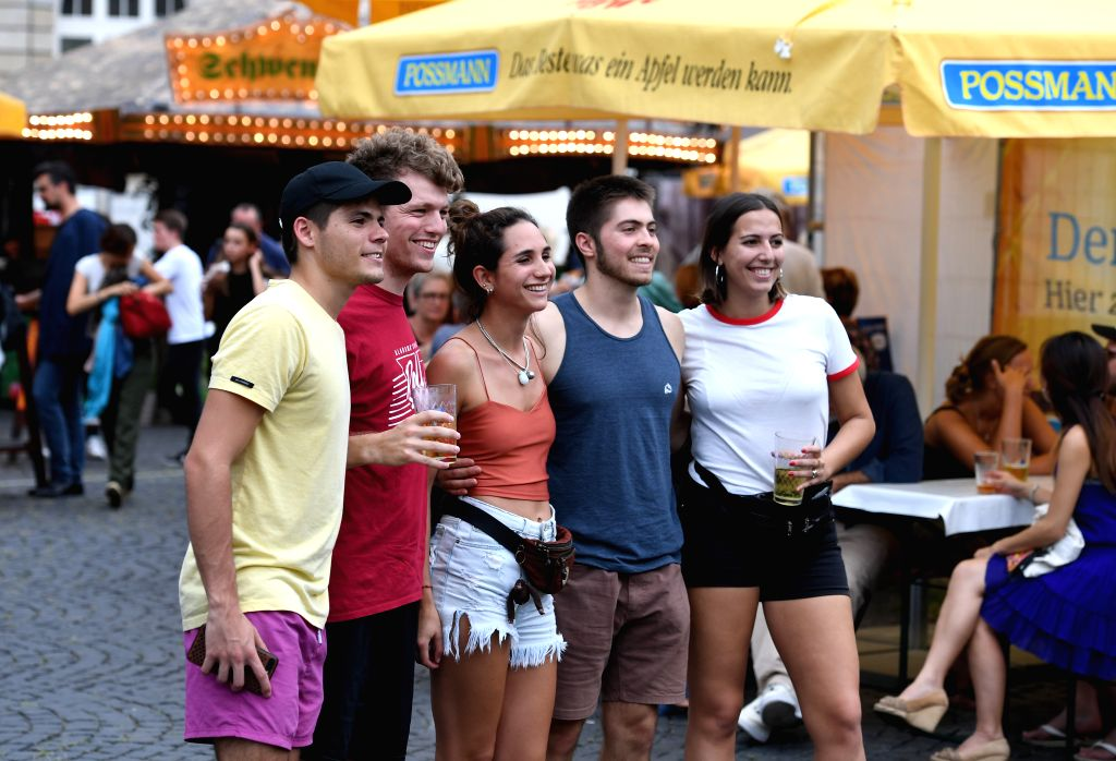 FRANKFURT, Aug. 9, 2019 - People pose for photos at the Frankfurt Apple Wine Festival in Frankfurt, Germany, on Aug. 9, 2019. The Frankfurt Apple Wine Festival is held here from Aug. 9 to 18. ...