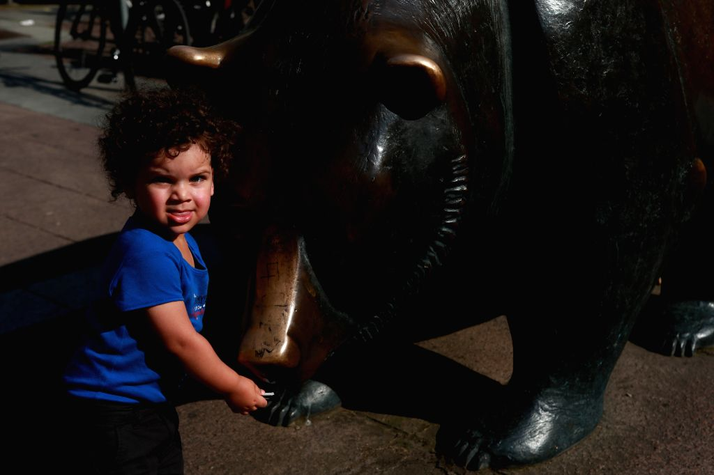 FRANKFURT, June 25, 2016 - A boy looks on by a copper bear sculpture outside the Frankfurt Stock Exchange in Frankfurt, Germany, June 24, 2016. The German share price index, DAX board, plunged 699.87 ...