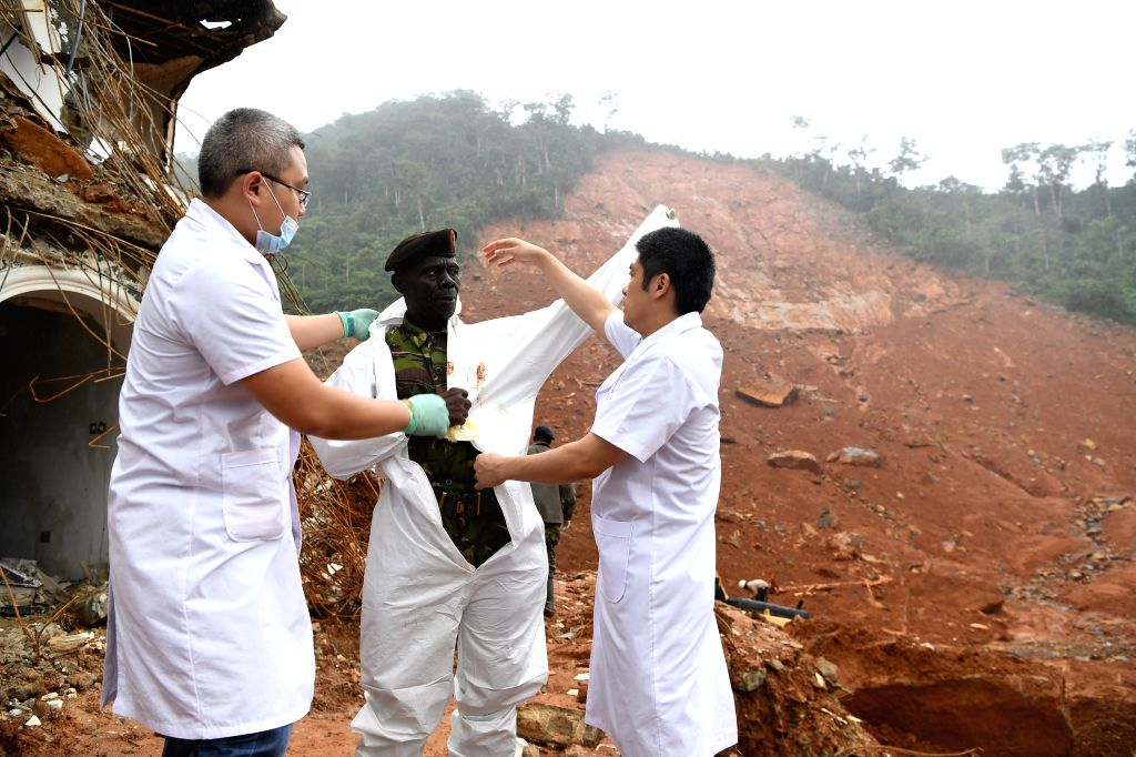 FREETOWN, Aug. 17, 2017 - Members of Chinese medical team help a rescuer (C) wear protective clothes at the mudslide site in Freetown, Sierra Leone, on Aug. 17, 2017. Chinese companies and medical ...