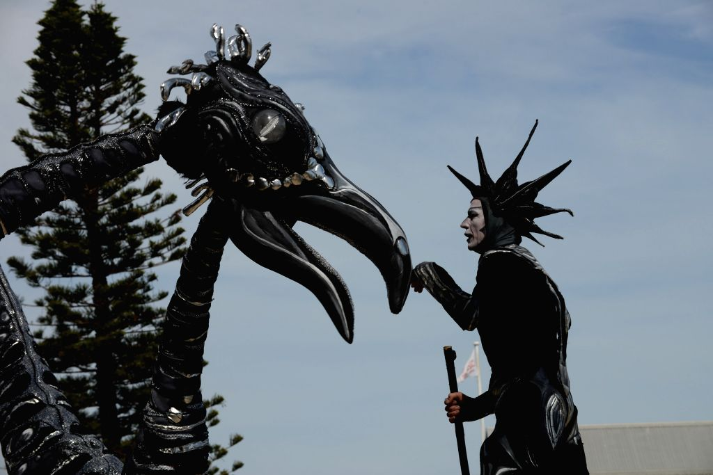 """A performer from the Netherlands shows a performance with a """"dinasour"""" in Fremantle, Australia, on April 20, 2014. Fremantle Street Art Festival is ..."""