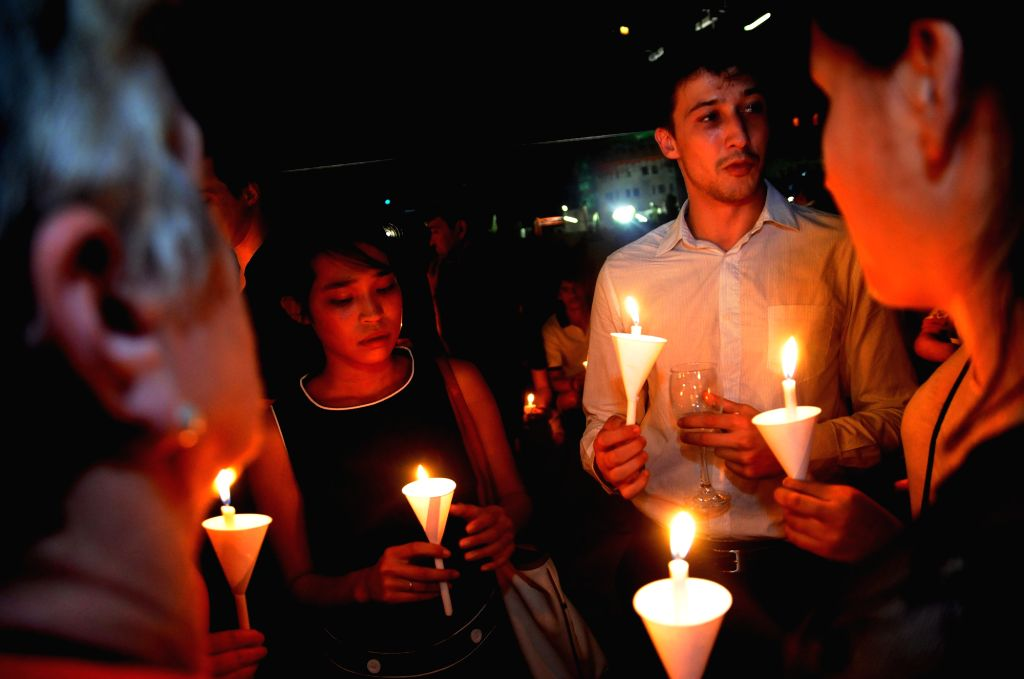 French people living in Thailand hold candles for the victims of Friday's attacks, in Bangkok, Thailand, Nov. 14, 2015. The provisional death toll of Paris attacks ...