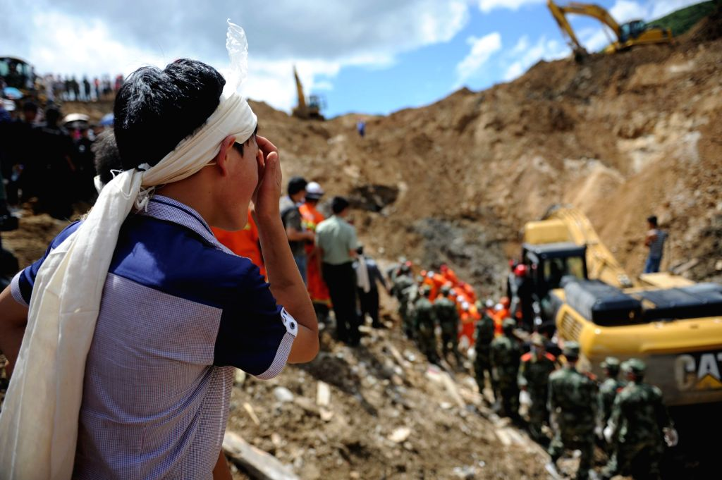 A relative of a victim waits at the site where a landslide occurred in Yingping Village of Daoping Township, Fuquan City, southwest China's Guizhou Province, Aug. ...