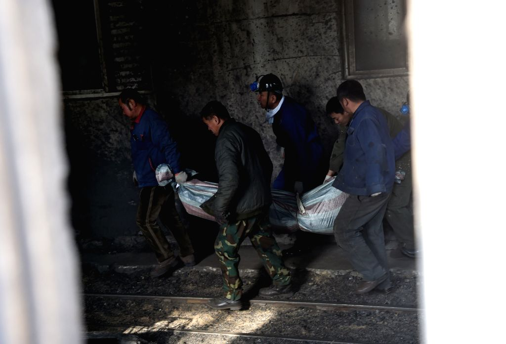 Fuxin (China): Rescuers carry the body of a victim from Hengda coal mine, a subsidiary of Fuxin Coal Corporation, in Fuxin, northeast China's Liaoning Province, Nov. 26, 2014. A fire occurred under ..