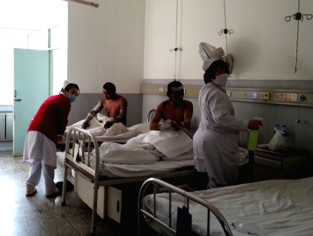 Fuxin (China): Two injured workers receive treatment at Ping'an Hospital of Fuxin Coal Corporation in Fuxin, northeast China's Liaoning Province, Nov. 26, 2014. A fire occurred under Hengda coal ...