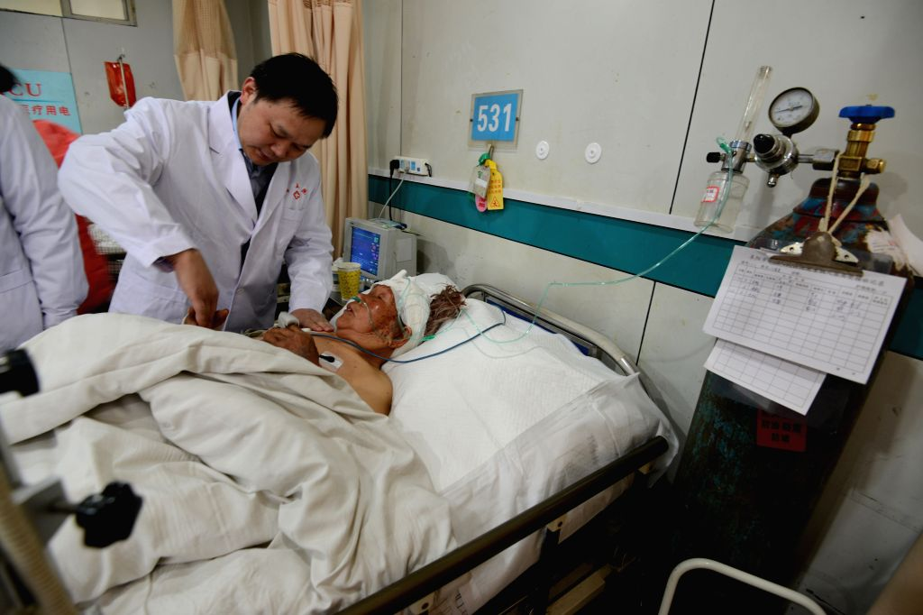 A wounded man receives treatment in a hospital in Fuyang, east China's Anhui Province, March 15, 2015. Two people have been killed, another 13 injured as of 9 p.m. ...