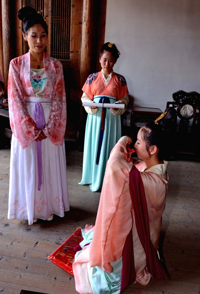 A girl (R) performs a hair-pinning ceremony, the Chinese traditional coming-of-age ritual for girls, in Fuzhou, capital of southeast China's Fujian Province, May 3, ...