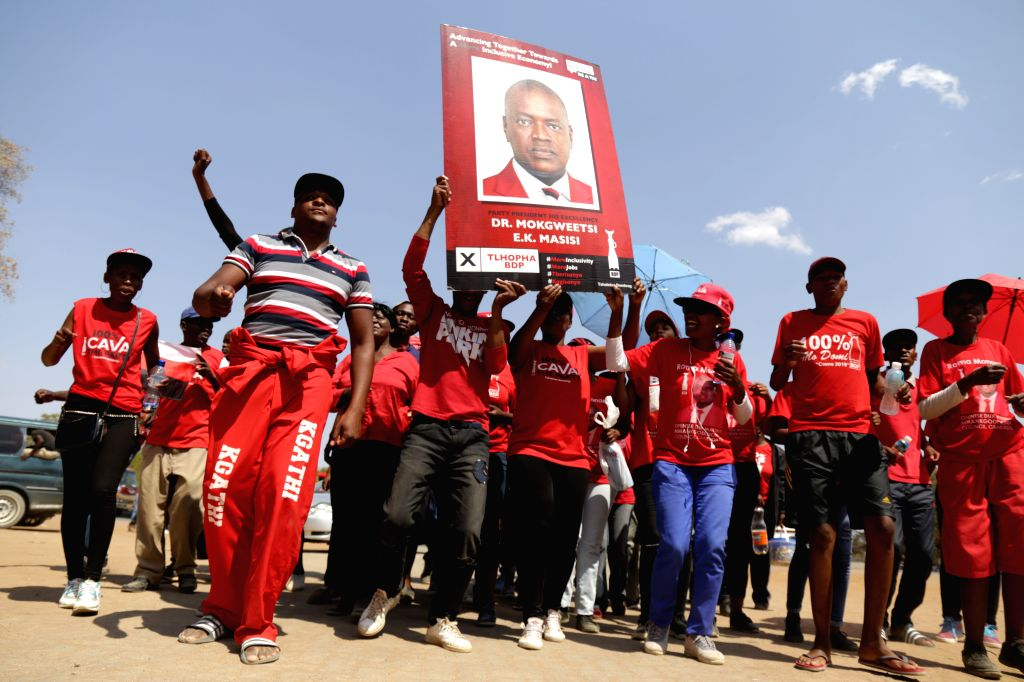 GABORONE, Oct. 24, 2019 - Supporters of the ruling Botswana Democratic Party (BDP) hold a poster of the party leader Mokgweetsi Masisi during a gathering as the ballot counting of the parliamentary ...