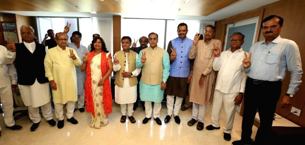 Gandhinagar: Gujarat Chief Minister Vijay Rupani with the four newly-elected legislators of Gujarat's ruling BJP - Jawahar Chawda (Manavadar), Asha Patel (Unjha), Purshottam Sabaria (Dhrangadhara) and Raghavji Patel (Jamnagar Rural), who were adminis - Vijay Rupani, Asha Patel and Raghavji Patel