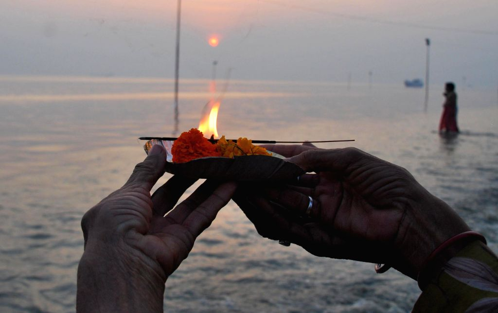 A devotee performs rituals at the  Gangasagar island, some 160 km south of Kolkata, a day ahead of `Makar Sankranti` on Jan 13, 2015.