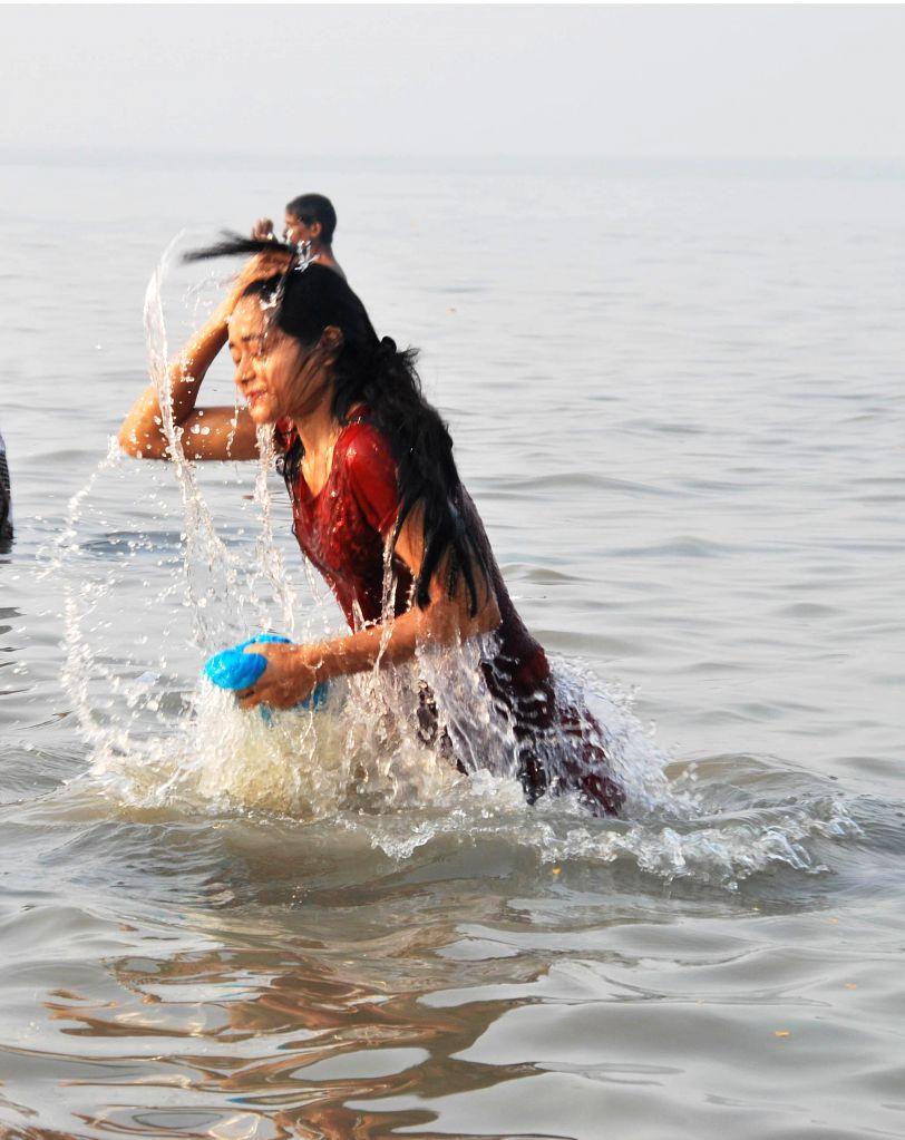 A lady takes holy dip at the Gangasagar island, on `Makar Sankranti`,  some 160 km south of Kolkata on Jan 15, 2015.