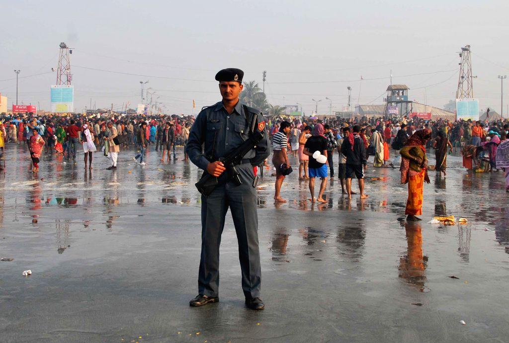 A soldier stands guard at the Gangasagar island, on `Makar Sankranti`,  some 160 km south of Kolkata on Jan 15, 2015.