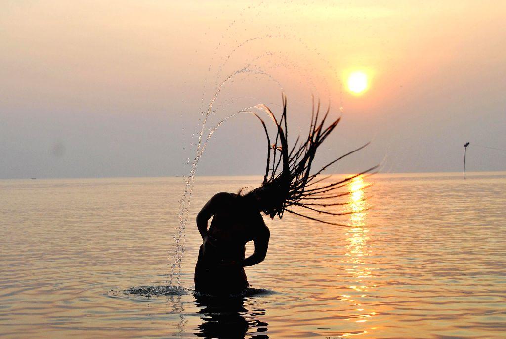 An ascetic takes a holy dip at the Gangasagar island, a day ahead of `Makar Sankranti`,  some 160 km south of Kolkata on Jan 13, 2015.