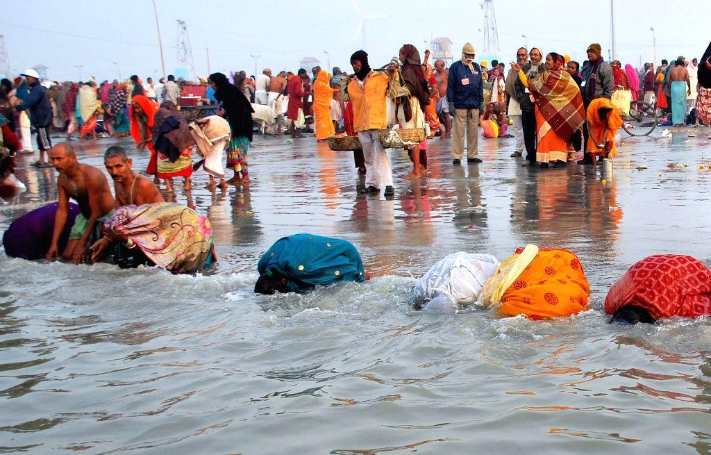 Devotees offer prayers on `Makar Sankranti` at the  Gangasagar island some 160 km south of Kolkata,  on Jan 14, 2015.