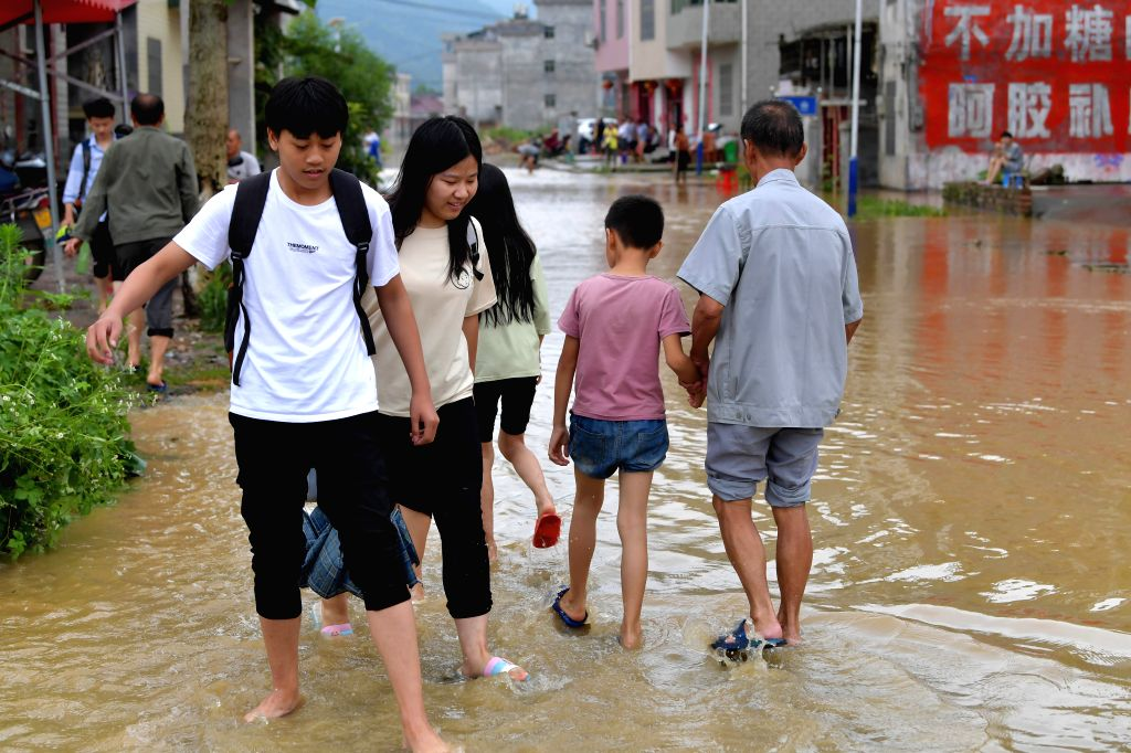 GANZHOU, June 11, 2019 - Local people wade through a waterlogged road in Zaizhong Township of Yongxin County, east China's Jiangxi Province, June 9, 2019. More than two million residents have been ...