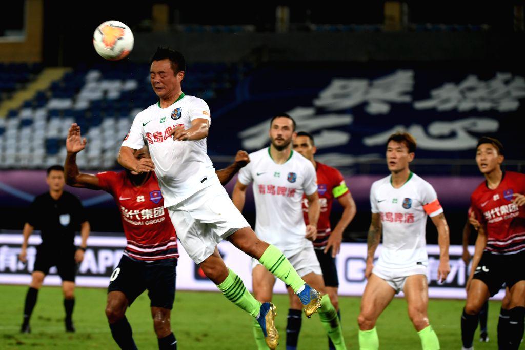 Gao Xiang (front L) of Qingdao Huanghai heads the ball during the 4th round match between Chongqing Dangdai Lifan and Qingdao Huanghai at the postponed 2020 season ...