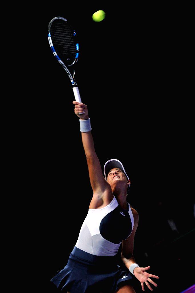 Garbine Muguruza of Spain serves during the WTA Finals round robin match against Lucie Safarova of the Czech Republic at Singapore Indoor Stadium in Singapore,  ...