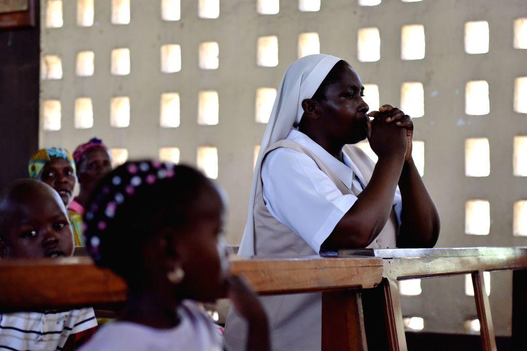 A nun prays during a commemorating service to mourn the victims during the campus attack in Garissa, Kenya, April 5, 2015./IANS