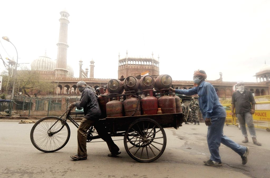 Gas delivery men struggle to push a cart loaded with LPG Gas cylinders outside India's largest mosque - The Jama Masjid - that remains deserted on the eve of Ramadan - the Muslim holy ...