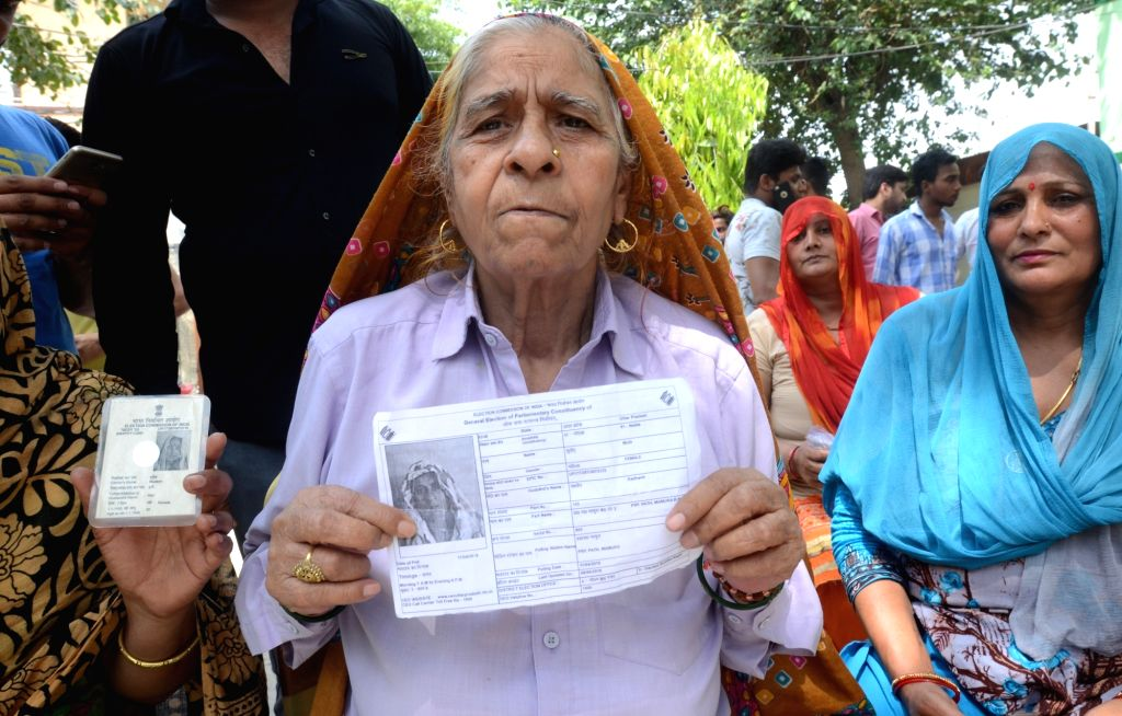 Gautam Buddh Nagar: A woman show her voter slips as she arrive to cast her vote for the first phase of 2019 Lok Sabha elections, at a polling booth in Uttar Pradesh's Gautam Buddh Nagar, on April 11, ...